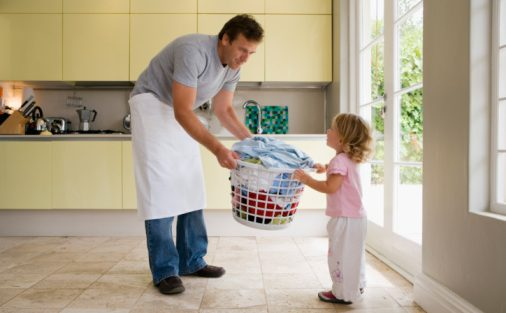 Father and child carrying laundry basket